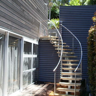 Curved stainless steel & wire on a single beam staircase